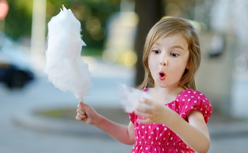 Adorable little girl eating candy-floss outdoors